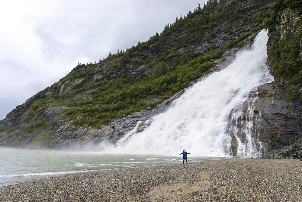 Visitor with outstretched arms on a beach in front of Nugget Falls Cascade, Mendenhall Lake and Glacier, Juneau, Alaska, United States of America, North America
