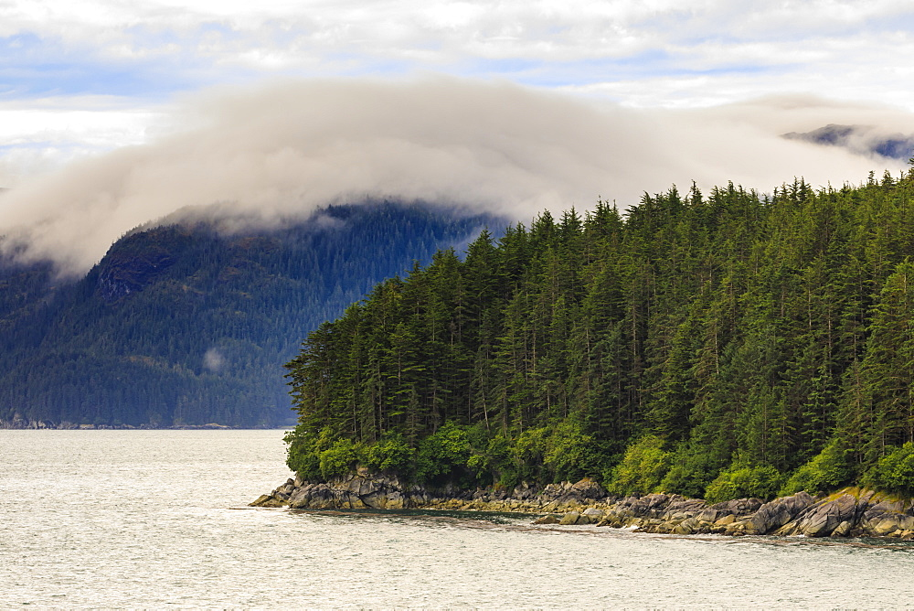 Mist, rocky shoreline and forest, Inian Islands, Icy Strait, between Chichagof Island and Glacier Bay National Park, Alaska, USA