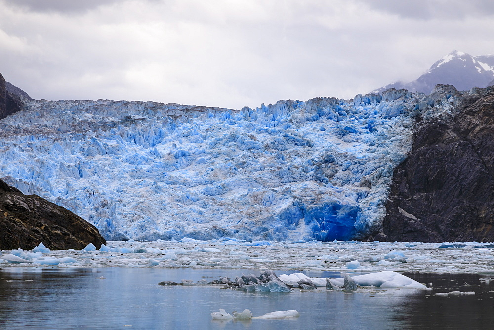 Ice pack and blue ice face of South Sawyer Glacier, mountain backdrop, Stikine Icefield, Tracy Arm Fjord, Alaska, USA - 1167-1650
