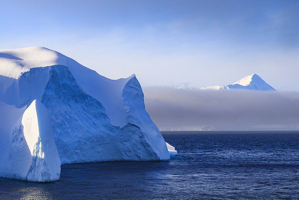 Huge iceberg, and mountain, clearing mist, Bransfield Strait, near South Shetland Islands and Antarctic Peninsula, Antarctica