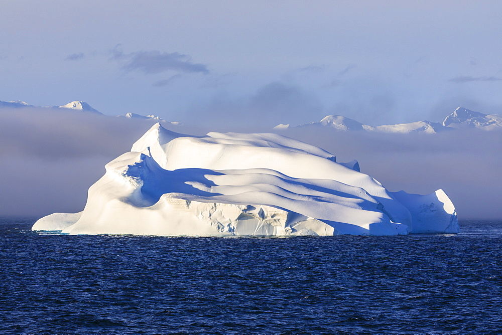 Huge iceberg, evening light, clearing mist, Bransfield Strait, near South Shetland Islands and Antarctic Peninsula, Antarctica