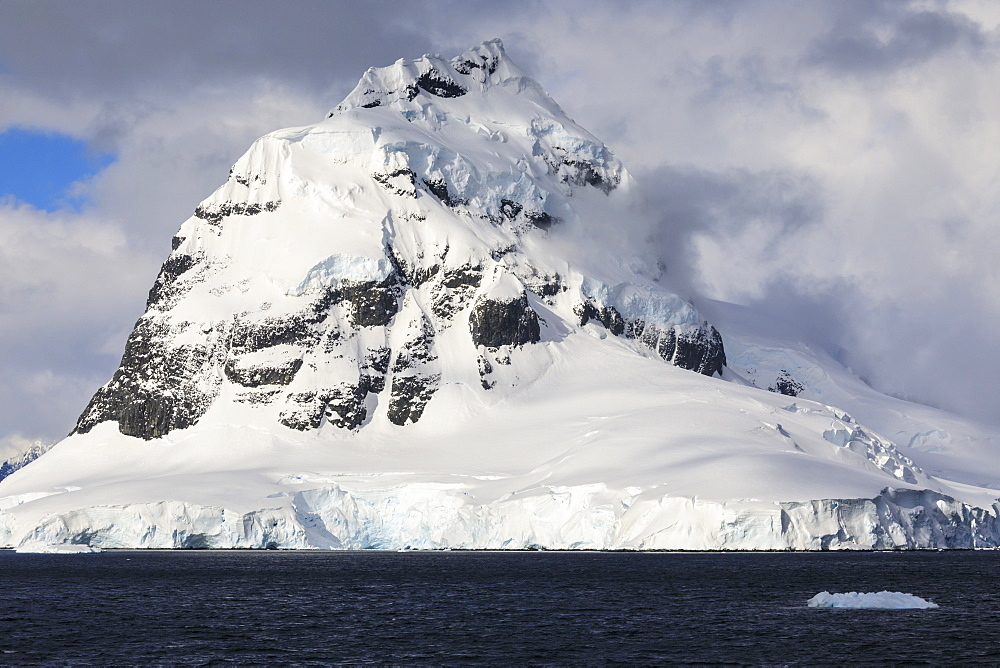Glaciers, pyramidal mountain peak and dramatic clouds and sky, Cape Errera, Wiencke Island, Antarctic Peninsula, Antarctica, Polar Regions