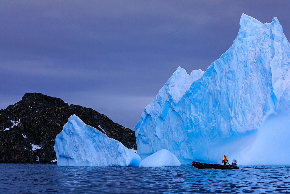 Person in zodiac looks at a huge blue iceberg, near Torgersen Island, Anvers Island, Antarctic Peninsula, Antarctica, Polar Regions