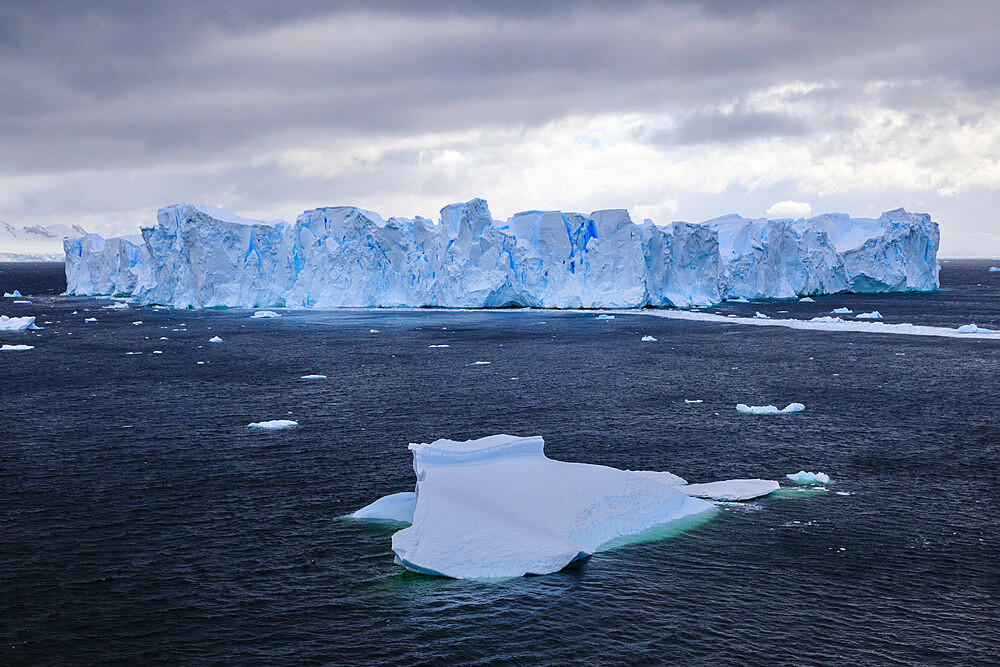 Large blue tabular iceberg, small iceberg and coast of Errera Channel, Danco Coast, Antarctic Peninsula, Antarctica, Polar Regions