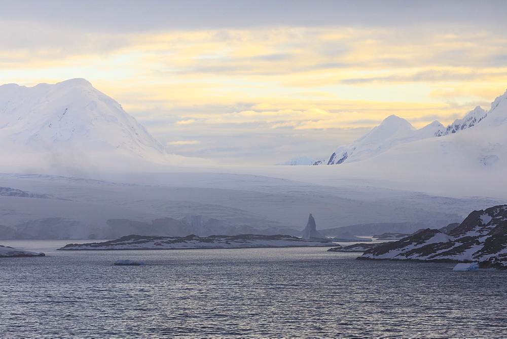 Sunrise, over misty mountains, tidewater glaciers and icebergs, Anvers Island, Antarctic Peninsula, Antarctica