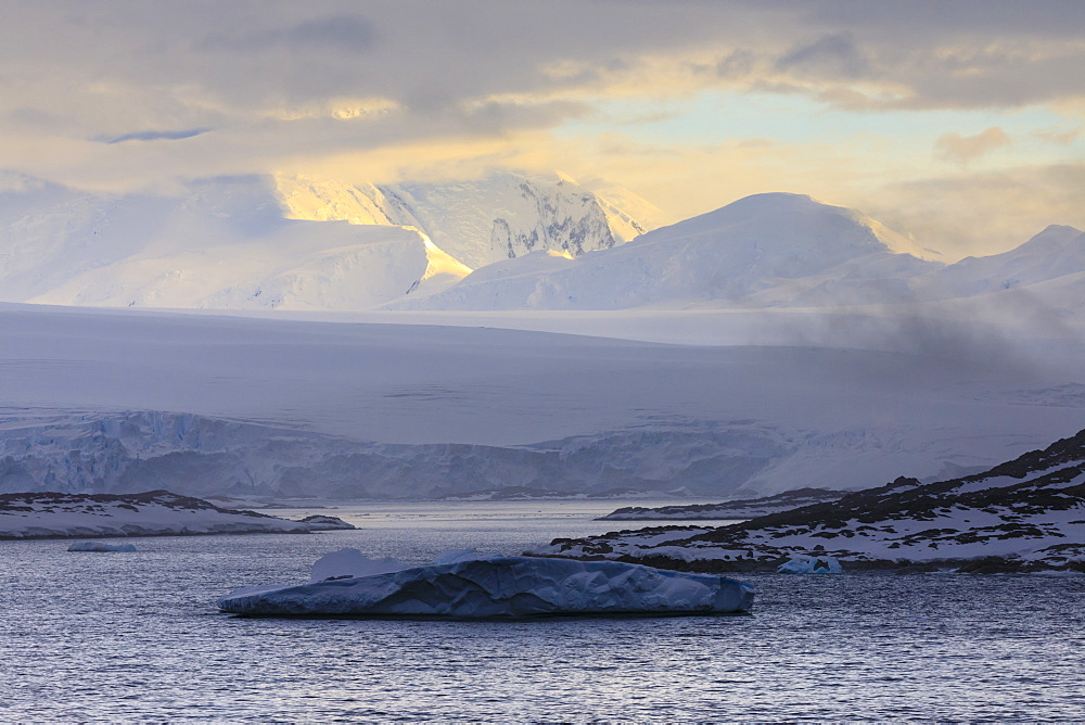 Sunrise, over misty mountains and tidewater glaciers, Anvers Island, Antarctic Peninsula, Antarctica