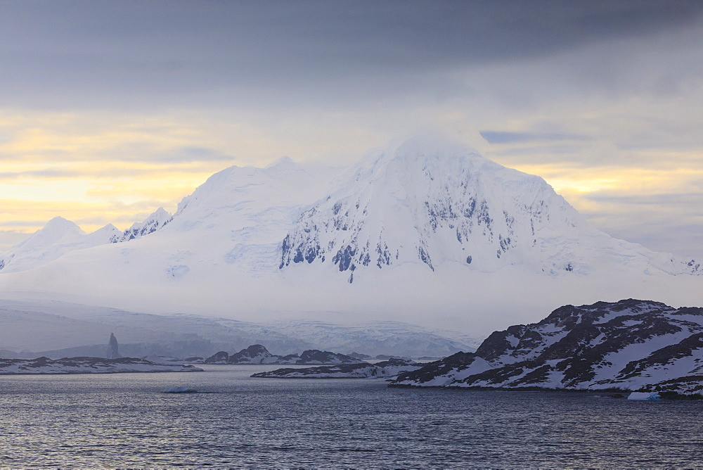 Misty Mount William at sunrise, rising from tidewater glaciers, Anvers Island, Antarctic Peninsula, Antarctica