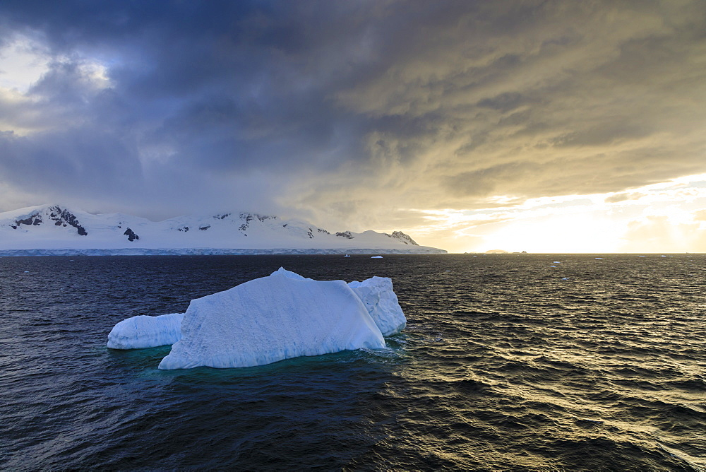 Blue iceberg at sunset, with interesting cloud formations, Gerlache Strait, Antarctic Peninsula, Antarctica