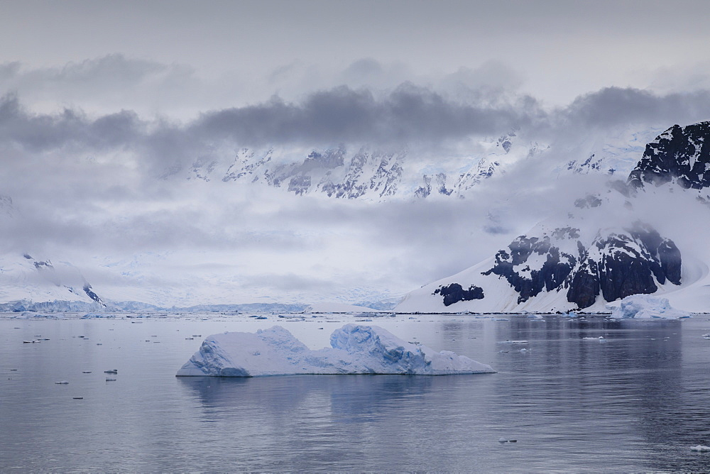 Low lying mist and clouds over mountains, glaciers and icebergs of Paradise Bay, calm waters, Antarctic Peninsula, Antarctica
