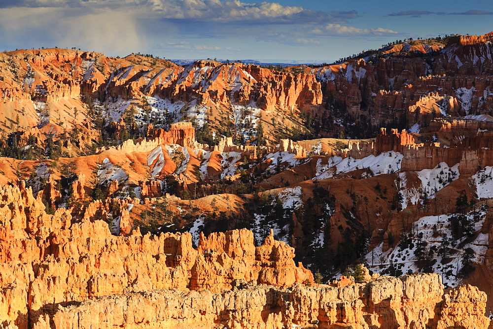 Late afternoon sun lights hoodoos and cliffs with a cloudy sky in winter, near Sunset Point, Bryce Canyon National Park, Utah, United States of America, North America