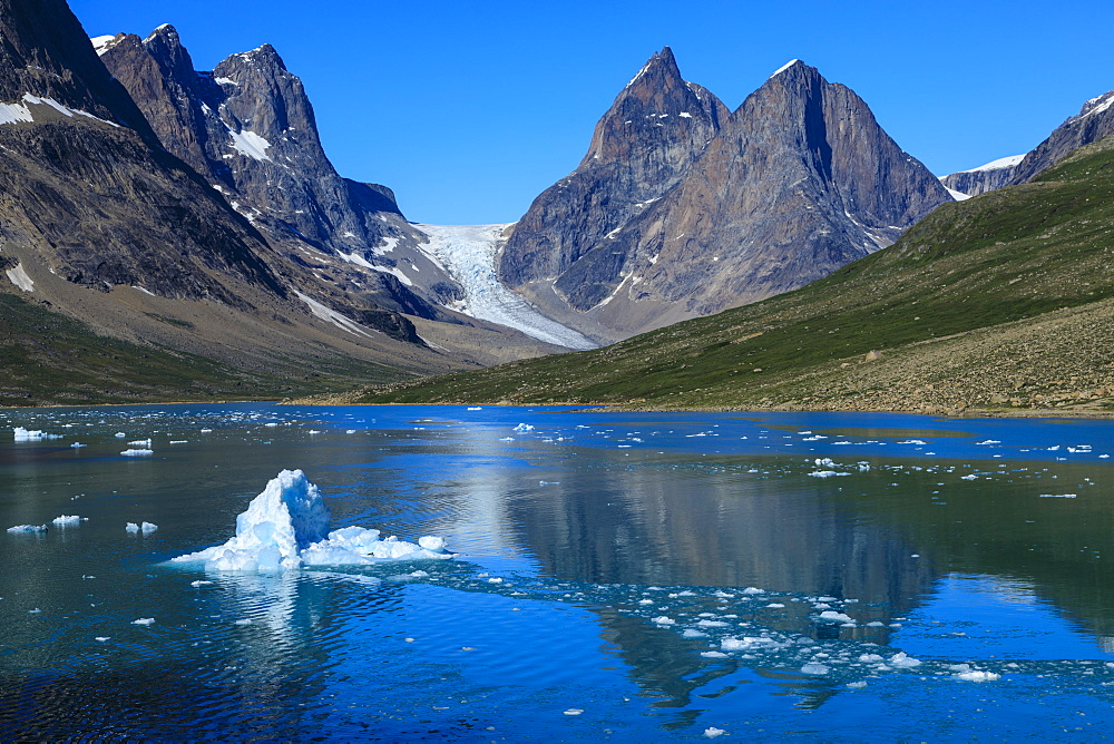 Blue iceberg, pyramidal peaks, glacier, rugged South Skjoldungen Fjord and Island, glorious weather, remote East Greenland
