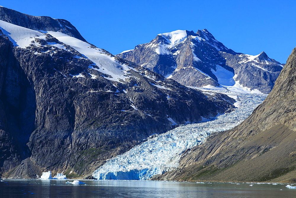 Mountains and tidewater glacier, rugged South Skjoldungen Fjord and Island, glorious weather, remote South East Greenland