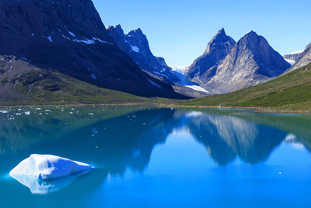 Iceberg, pyramidal peaks, reflections, blue green waters, South Skjoldungen Fjord, glorious weather, remote South East Greenland