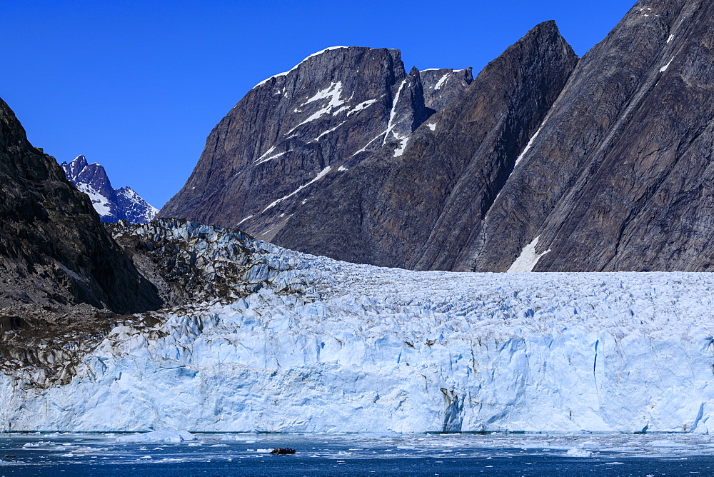 Cruise passengers in zodiac give scale to huge face, Thryms Glacier, Skjoldungen Fjord, glorious weather, remote East Greenland