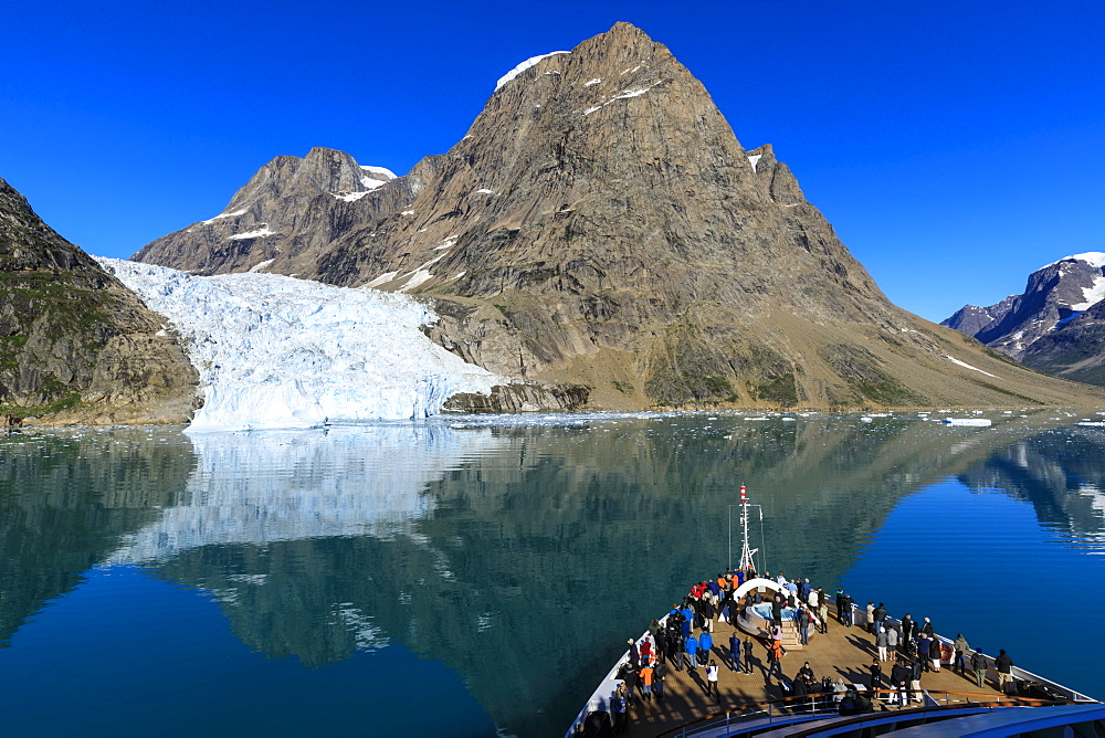 Expedition cruise ship and passengers, tidewater glacier, South Skjoldungen Fjord, glorious weather, remote East Greenland