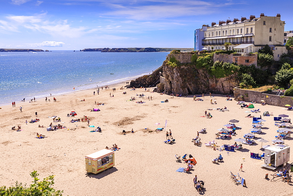 Castle Beach, historic houses above the cliffs, sunbathers on a sunny day in summer, Tenby, Pembrokeshire, Wales, United Kingdom, Europe