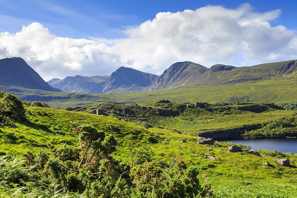 Mountains by fields in Coigach, Scotland, Europe