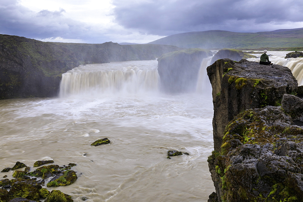 Lady sits cross legged on a rock overlooking Godafoss (Waterfall of the Gods), long exposure, Summer, outside Akureyri, Iceland