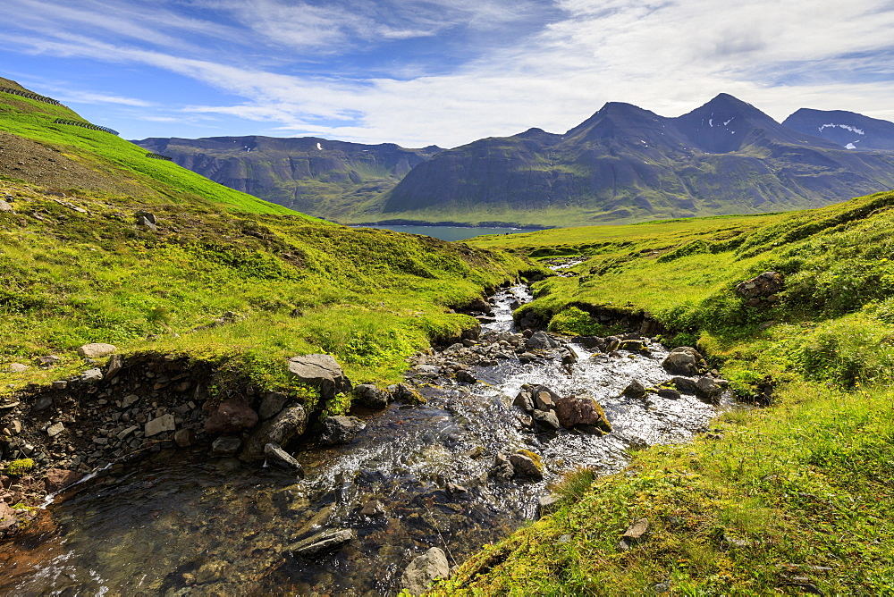 Stream runs through lush, green Hvanneyrarskal, hanging valley above Siglufjordur, fjord view, Summer, North Iceland