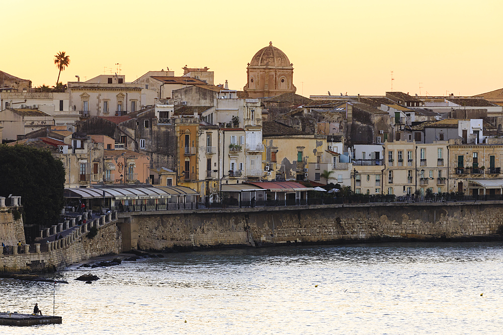 Sunrise over Ortigia (Ortygia), from the sea, fisherman on pier, Syracuse (Siracusa), UNESCO World Heritage Site, Sicily, Italy