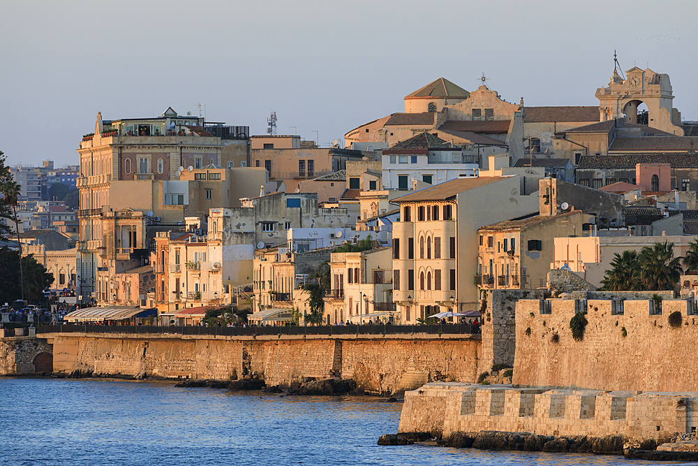 Sunset lights up Ortigia (Ortygia), from the sea, Syracuse (Siracusa), UNESCO World Heritage Site, Sicily, Italy