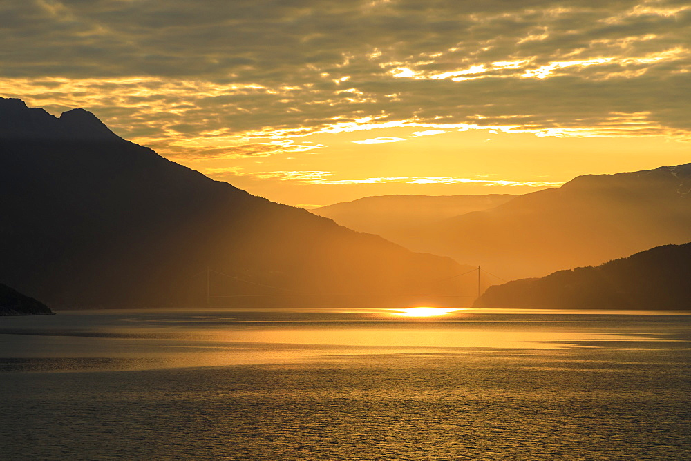 Stunning sunrise over the huge Hardanger Bridge, misty dawn, beautiful clouds, Hardangerfjord, Norwegian Western Fjords, Norway, Scandinavia, Europe