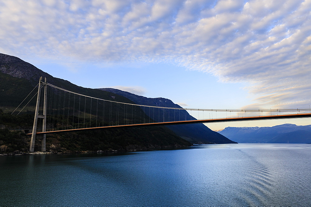 Passing under the huge Hardanger Bridge, sunrise, beautiful dawn clouds, Hardangerfjord, Norwegian Western Fjords, Norway, Scandinavia, Europe
