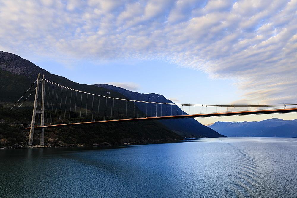 Passing under the huge Hardanger Bridge, sunrise, beautiful dawn clouds, Hardangerfjord, Norwegian Western Fjords, Norway