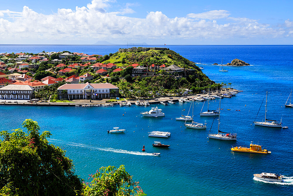 Elevated view over anchored yachts to Fort Oscar, passing small boats, Gustavia, St. Barthelemy (St. Barts) (St. Barth), West Indies, Caribbean, Central America