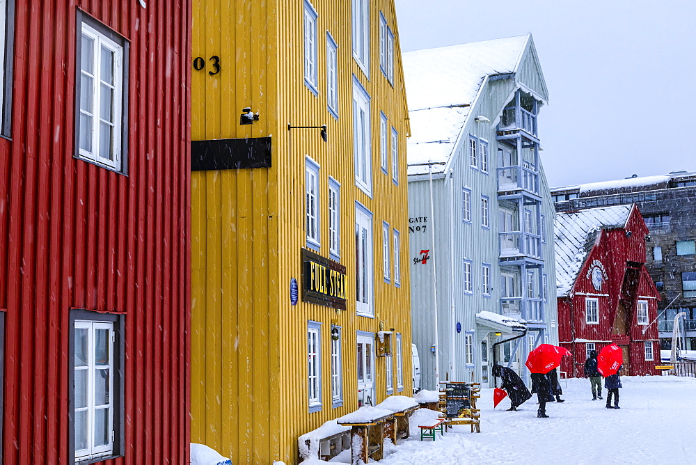 Tourists, colourful historic wooden buildings, heavy snow in winter, Tromso, Troms og Finnmark, Arctic Circle, North Norway, Scandinavia, Europe