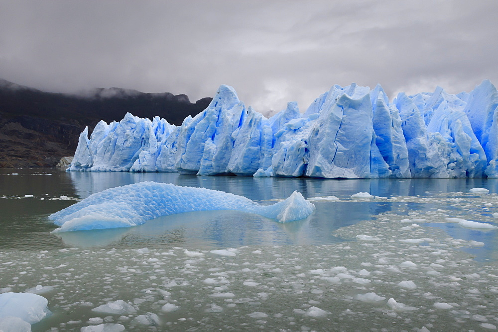 Lake-level view of blue ice at the glacier face and iceberg, Grey Glacier, Torres del Paine National Park, Patagonia, Chile, South America