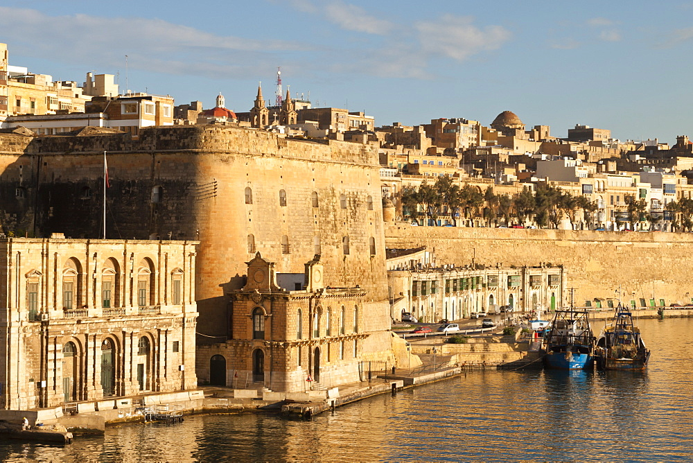 Fishing boats at the Barriera Wharf and Grand Harbour fortifications in the golden early morning, Valletta, Malta, Mediterranean, Europe