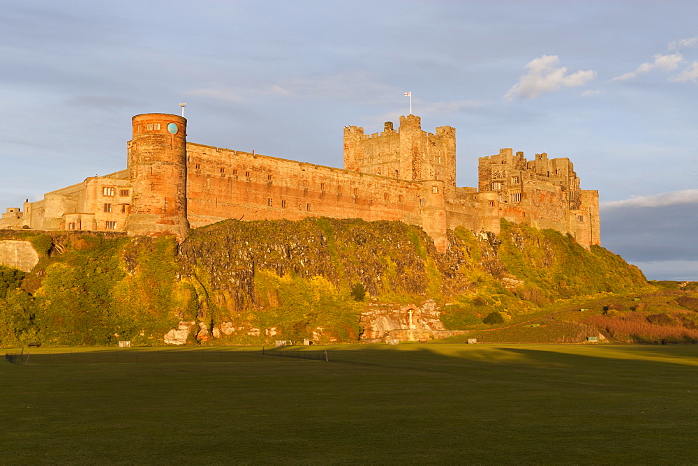 Bamburgh Castle and Cricket Green in evening sunshine, Bamburgh, Northumberland, England, United Kingdom, Europe