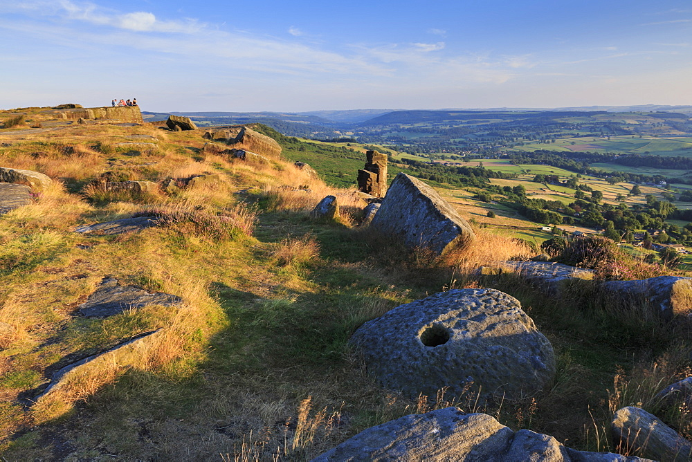 Friends on Curbar Edge with boulders and a millstone in summer, Peak District National Park, Derbyshire, England, United Kingdom, Europe