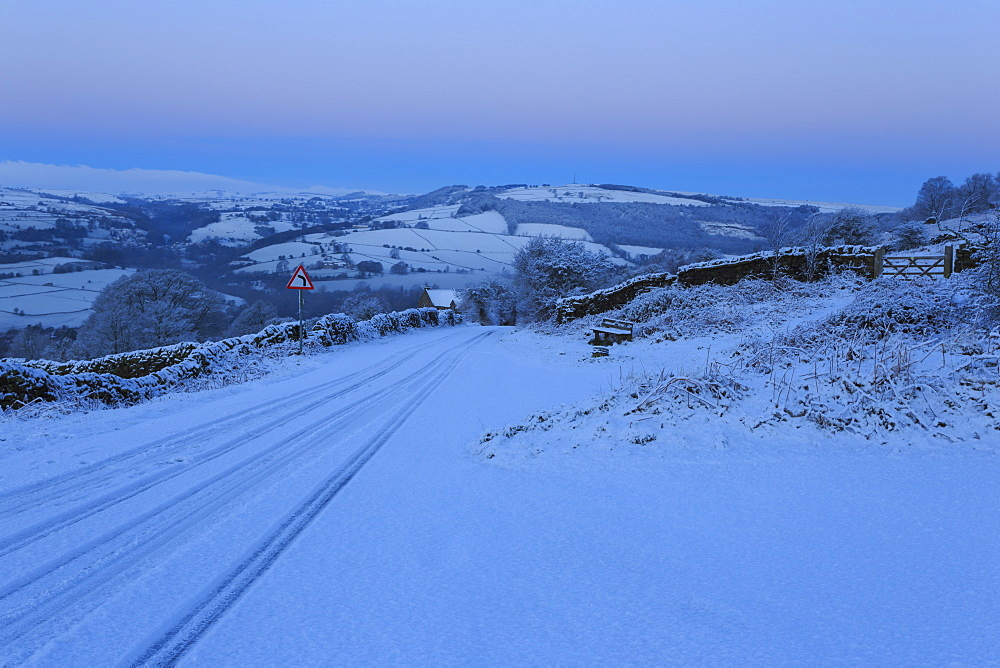 Fresh snow on country lane, winter pre-dawn blue hour, below Curbar Edge, Peak District National Park, Derbyshire, England, United Kingdom, Europe
