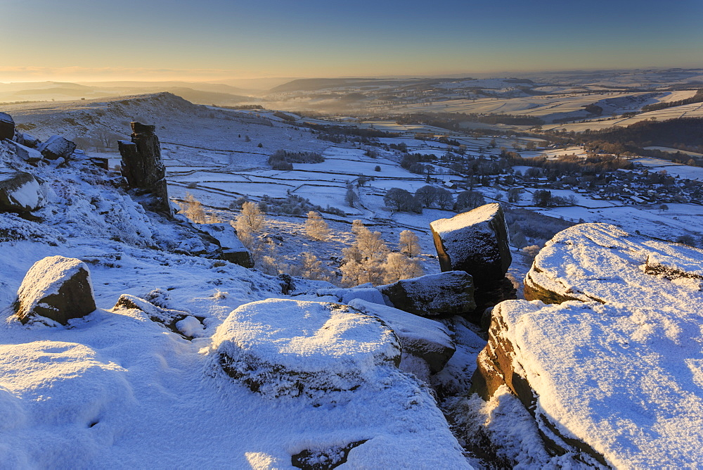 Snow on millstone lit by sunrise, Curbar and Baslow Edge with misty hills and wintry trees, Peak District, Derbyshire, England, United Kingdom, Europe