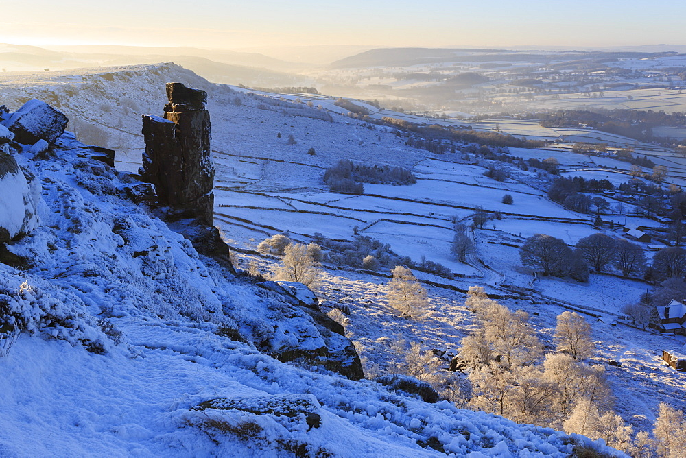 Fresh snow on Curbar and Baslow Edge with misty Derwent valley and winter trees, Peak District, Derbyshire, England, United Kingdom, Europe