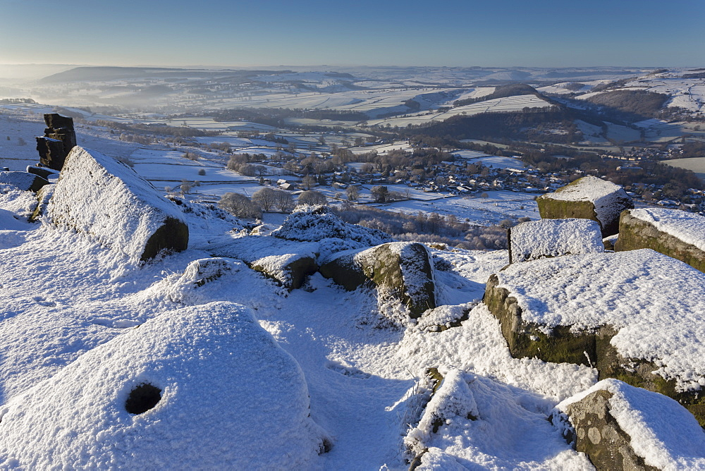 Fresh snow on millstone, Curbar Edge, misty Derwent Valley with Curbar and Baslow villages, Peak District, Derbyshire, England, United Kingdom, Europe