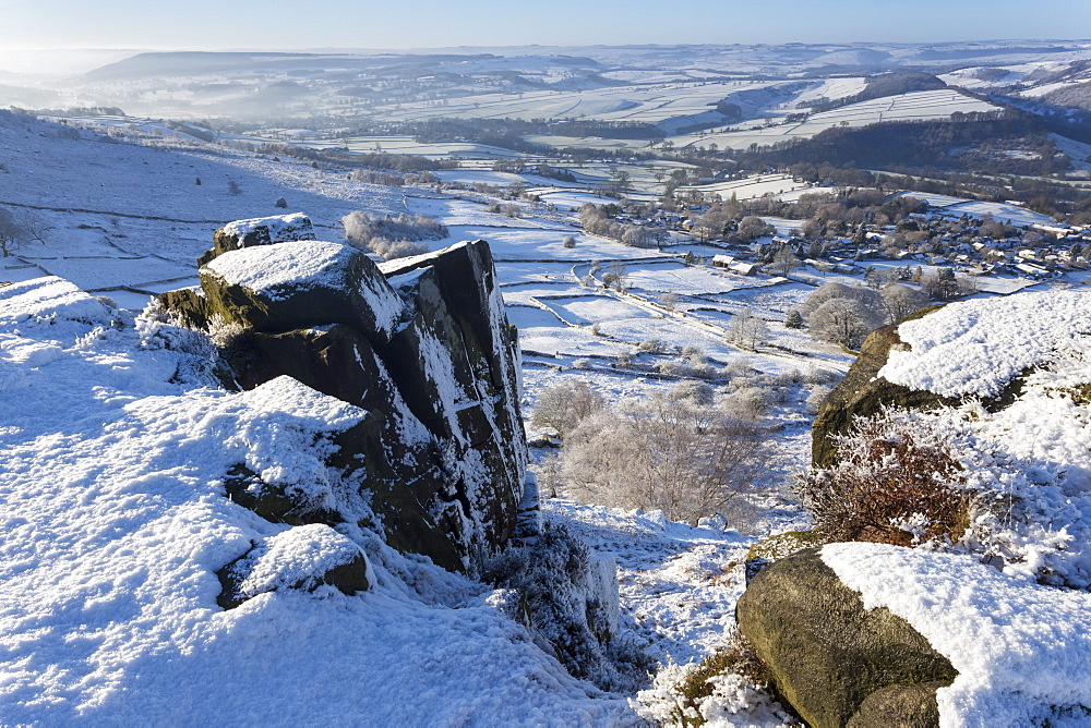 Snowy Curbar village beyond the rocks of Curbar Edge, winter morning, Peak District National Park, Derbyshire, England, United Kingdom, Europe