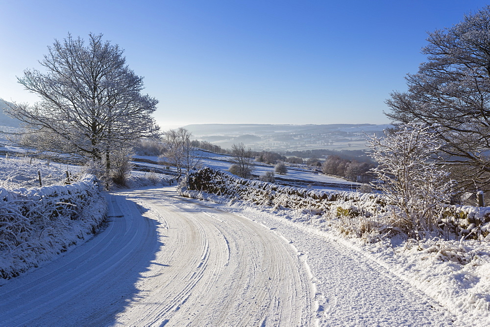Snowy, bendy country lane with stone walls and trees, Curbar Edge, Peak District National Park, Derbyshire, England, United Kingdom, Europe