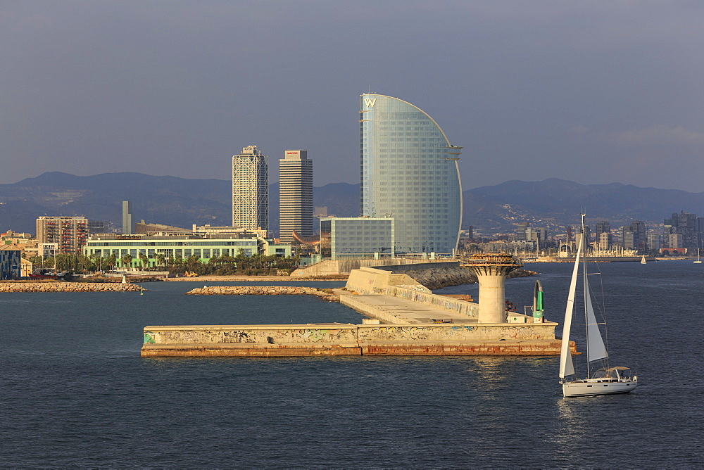 Yacht sails past La Barceloneta and the waterfront, Port Olimpic in distance, late afternoon, Barcelona, Catalonia, Spain, Europe