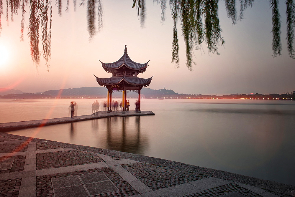 Visitors are taking the last shots with a pagoda at West Lake as the sun is sinking, Hangzhou, Zhejiang, China, Asia