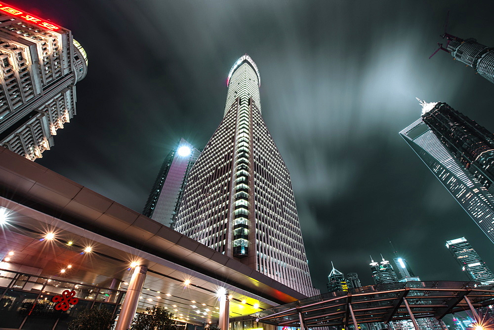 Low angle view of skyscrapers in Shanghai Pudong at night, with moving clouds, Shanghai, China, Asia