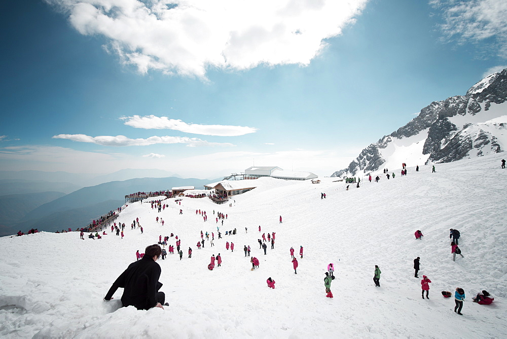 Mostly local tourists playing in the snow on top of Jade Dragon Snow Mountain near Lijiang, Yunnan province, China, Asia