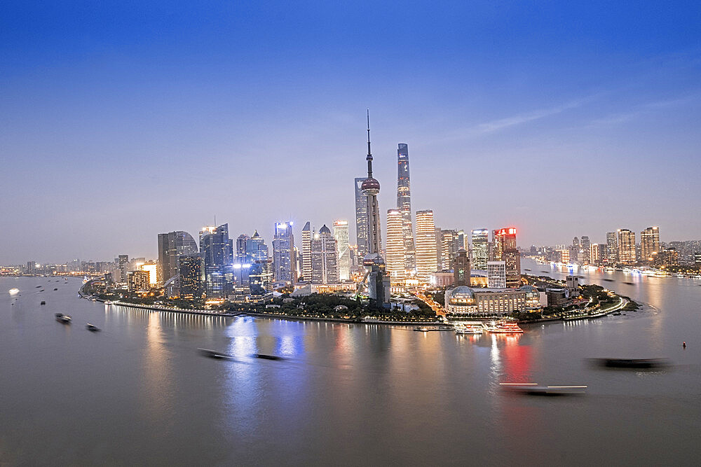 The illuminated skyline of Pudong district in Shanghai with the Huangpu River in the foreground