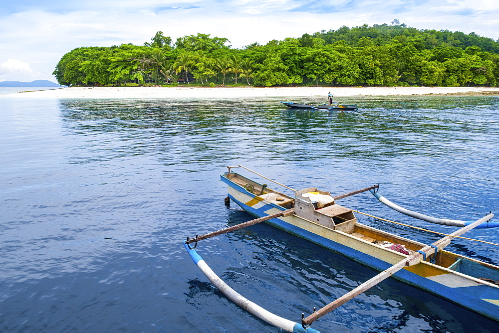 Indonesia, Spice Islands, Ambon, Molana island. A local fisherman and a traditional outrigger canoe off the beach.