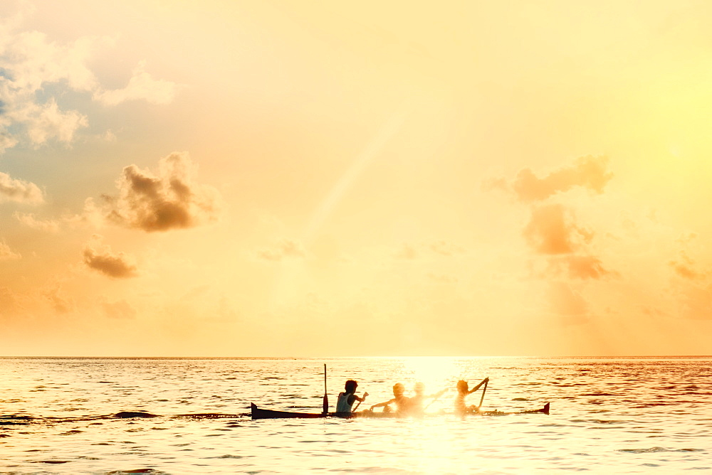 Indonesia, Spice Islands, Banda. Local boys on a wooden canoe at sunset
