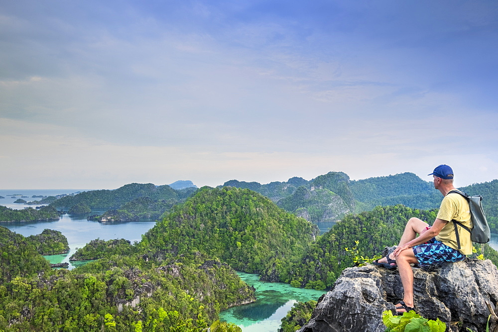 A tourist looking out over a bay of islands from Harfat mountain, Spice Islands, West Papua, Indonesia, Southeast Asia, Asia