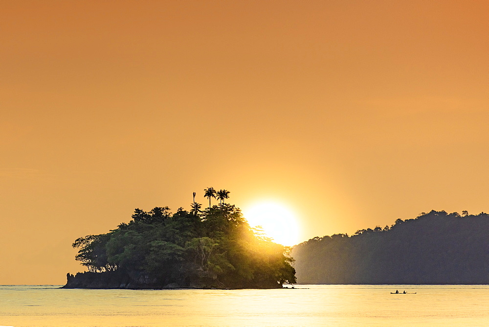 The sun setting behind islets in the Banda archipelago, Banda, Maluku, Spice Islands, Indonesia, Southeast Asia, Asia