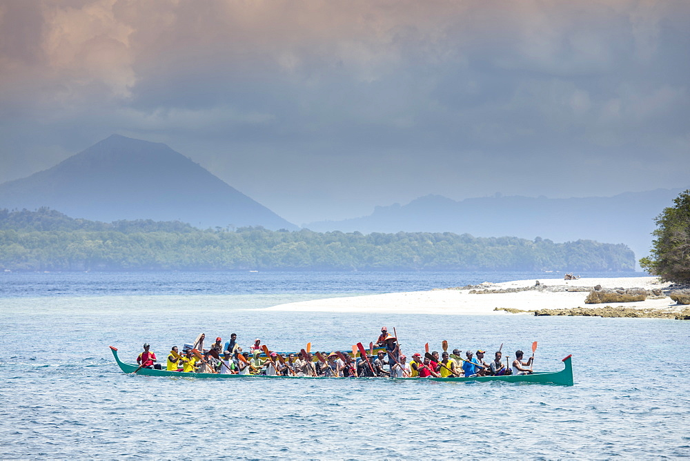 Locals in a traditional wooden Korakora racing canoe with the cone of Gunung Api Wetar behind, Rhun, Banda Islands, Maluku, Spice Islands, Indonesia, Southeast Asia, Asia - 1176-1157